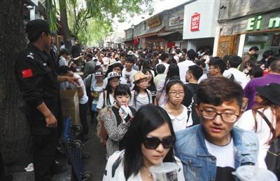 """昨天,""""五一""""小长假第一天,南锣鼓巷迎来旅客顶峰,但因为停息欢迎团队游,客流比客岁削减2.3万人次。新京报记者 王贵彬 摄"""