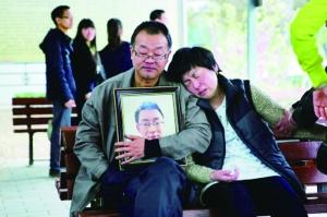 陕西咸阳,离别仪式事后,魏则西的尸体被推去火葬,爸爸妈妈坐在殡仪馆外等待 《法制晚报》供图