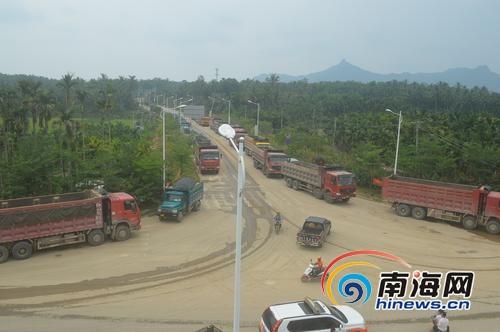 停在椰子寨村委会丁字路口等待运砂的改装卡车。