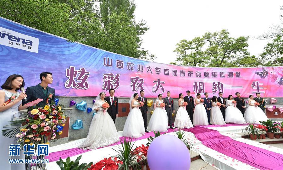 """这是5月7日拍摄的山西农业大学青年教师集体婚礼现场。当日,一场以""""炫彩农大·相约一生""""为主题的青年教师集体婚礼在山西农业大学举行,八对新人在学校师生的共同见证下携手走进婚姻殿堂。新华社发(曹阳摄)"""