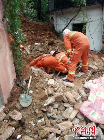 5月8日,消防官兵在塌方地点,用毯子清理房屋周围淤泥,门卫室已经出现裂缝,有坍塌的危险。 李龙 摄