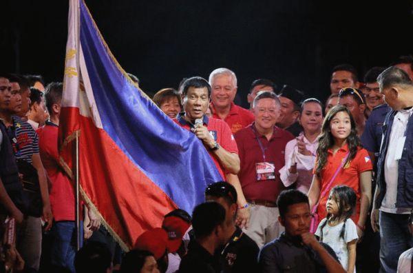 在一次竞选活动中,杜特蒂拿着菲律宾国旗 来源:CBS