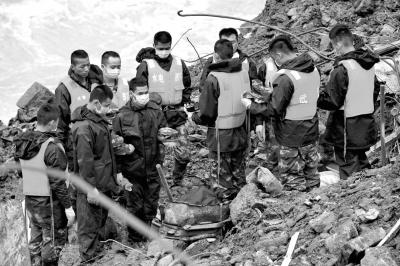 5月9日,营救职员在灾祸现场向罹难者致哀。新华社发
