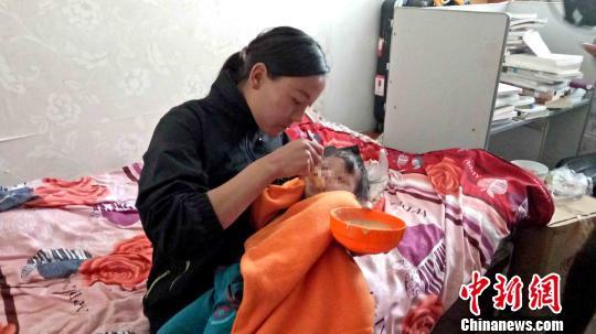 图为10日上午,在青海农牧民之家的住处,卓玛才仁正在给阿吉喂饭。 张海雯 摄
