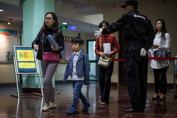 2016年5月7日,上海,一位男孩在家长的陪同下排队进入学校大厅准备参加参加幼升小面试。