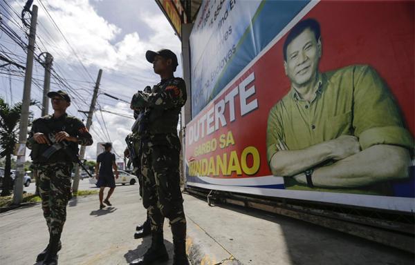 本地时刻2016年5月16日,菲律宾战士保卫在罗德里戈・杜特尔特的画像前。东方IC 图