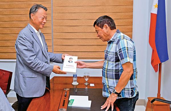 国家驻菲律宾大使赵鉴华(左)16日赠予英文版《习近平谈治国理政》一书给菲律宾候任总统杜特尔特。至公网 图