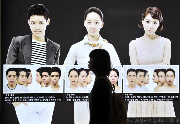 韩国首尔,一名妇女从地铁站的巨型整容广告前走过。 视觉中国 资料