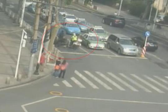 图为武汉市洪山路东三路口视频截图,红圈内为交警驾驶摩托车准备拦截涉事拖拉机。