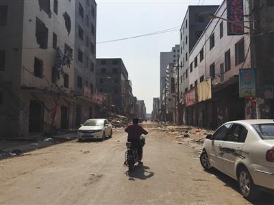 5月11日,郑州北郊薛岗村,一名乡民骑车通过拆迁的大街。头一天,拆迁户范华培持刀杀死三人轻伤一人后,被警方击毙。