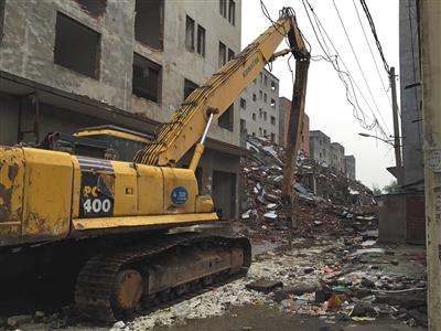 5月14日,一辆发掘机在薛岗村拆迁工地,周围都是乡民违建盖的高楼。