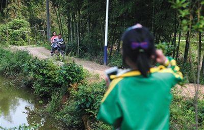 5月13日,湖南省长沙市宁乡县流沙河镇高山村,莎莎在家门口看着爷爷载姐姐回家,姐姐在寄宿初中上学,只有周末才能回家。