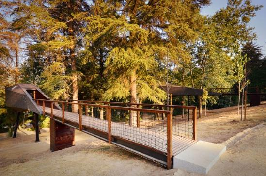在葡萄牙的Pedras Salgadas生态度假村,建筑师Luís Rebelo de Andrade和Tiago Rebelo de Andrade在一片树木中设计和搭建了两座树蛇木屋(Tree Snake Houses) 。为了减少对自然环境的影响,木屋采用预制和现场组装的方式安装在高高的木跷上。通过一道不太长的长廊进入,木屋内拥有一个小厨房 、浴室、以及附有工作空间的主卧室,住宿于此的旅客可以透过前置观景窗和天窗欣赏到郁郁葱葱的树林或星空。