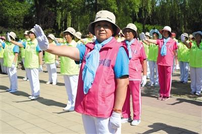 """5月24日,数十名自愿者在大兴区亦庄广博公园为社区大众扮演""""控烟操"""",做出控烟手势。新京报记者 吴江 摄"""