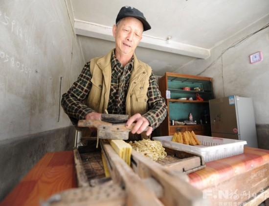 用传统东西将成型豆腐切丝后销售。