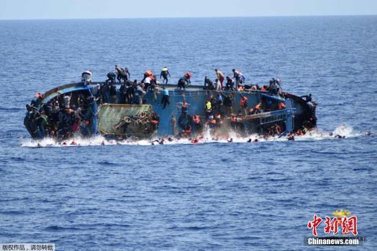 资料图:一艘满载难民的船只即将倾覆,船上的难民纷纷跳海逃生。