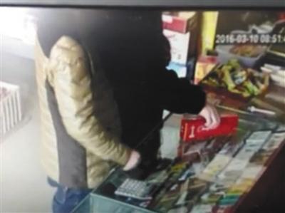 一家超市老板提供的监控显示,一名男子趁老板不注意,将真烟装进衣服,旁边一男子迅速掏出假烟放在前台替代。