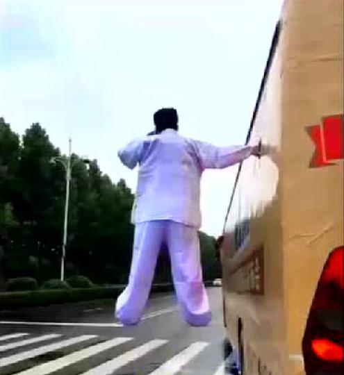 """身穿红色衣物的女子右手紧紧吸在车上,两脚""""悬浮"""",左手还时时接打德律风。 视频截图 摄"""