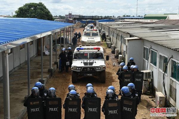 中国第四支驻利比里亚维和警察防暴队应急处突分队依托装甲车,组成防暴处突队形,进行掩护推进。