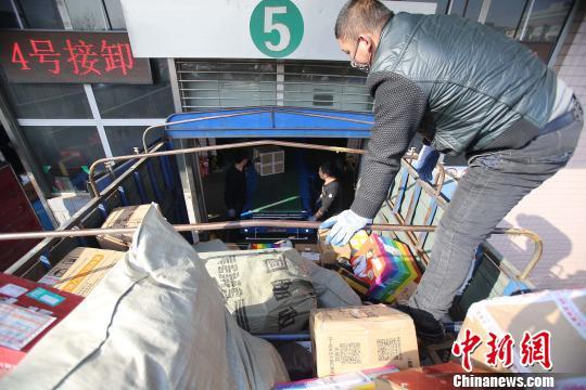 资料图:山西太原,邮政工作人员正在给快递包裹装车。张云 摄