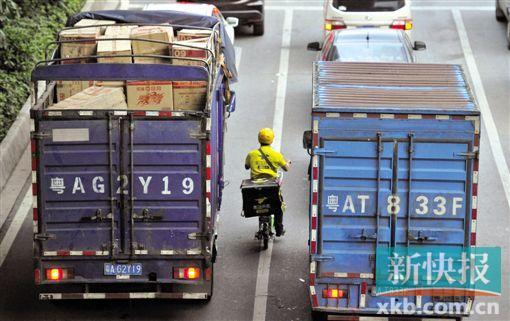 在白云区金沙洲路与环洲三路穿插路口,送外卖者骑单车穿越在两辆货车之间。