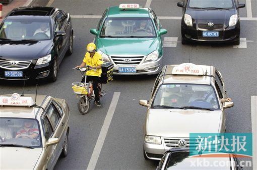 在河汉区中山小道棠下村路段,送外卖者骑电动车在灵活车道随便穿行。