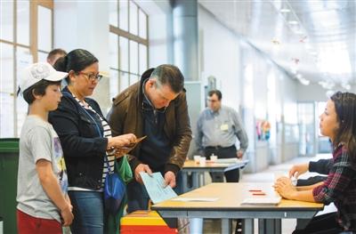 5日,在瑞士日内瓦一处投票站,当地居民参加全民公投。