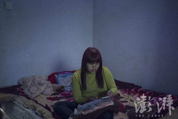2016年3月29日,Sophorn坐在床上一边叠衣物一边玩手机。她正在拾掇要带回柬埔寨的行李。本文图像 丛妍 磅礴新闻记者 陈荣辉 图
