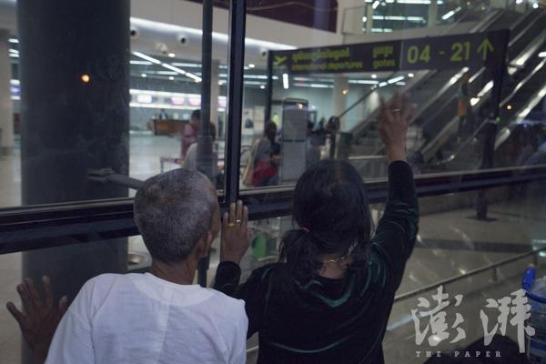 2016年5月3日,Sophorn走上扶梯进入动身地区前,她的母亲和家人在机场外隔着玻璃窗向她挥手辞别。