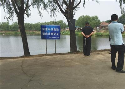 """昨天,事发鱼塘四周没有围栏,警示牌上写着""""河流水深风险,请您注重安全""""字样。"""
