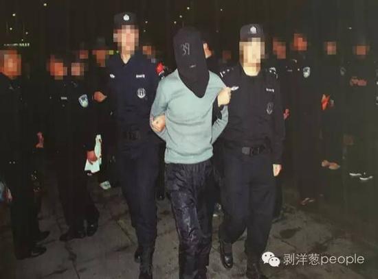 """乌拉特中旗公安局大厅展板上关于""""1.02""""案子中,押送犯法怀疑人的图像。新京报记者 尹亚飞 摄"""