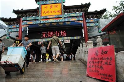 昨天,十里河天娇文明城,门口的通告牌上写着每周四夜间的鱼市营业的音讯。新京报记者 薛�B 摄
