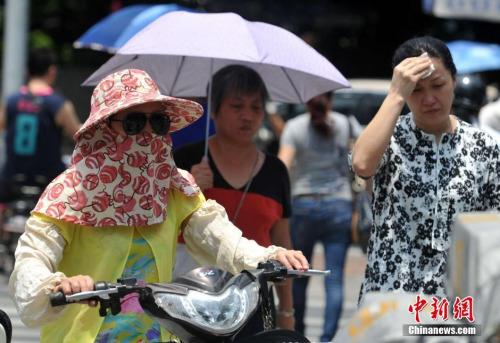 """资料图:6月1日,有着""""新四大火炉""""之称的福州发布高温橙色预警信号,各县市最高气温将升至35℃以上,内陆县市最高气温可达37-38℃。图为福州市民冒着高温出行。 张斌 摄"""
