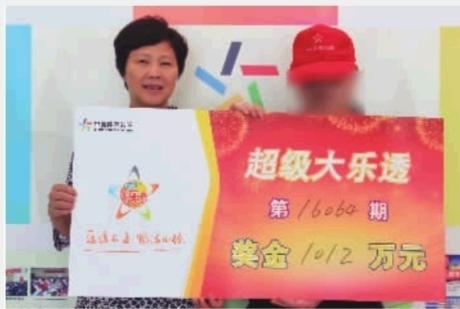 湖南省体彩中心副主任朱卫霞与大奖得主合影。