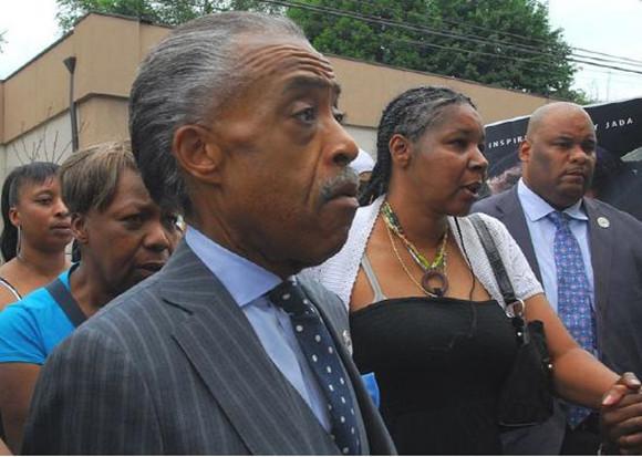 (美国非裔美国人浸信会牧师,民权运动、社会正义运动家,电台及电视节目主持人Al Sharpton 和Garner遗孀Esaw Garner (右二)在Staten Island于2014年七月19日, 2014的抗议活动上的照片。)