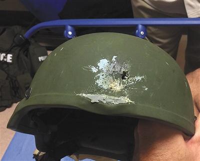 与枪手枪战时一警员被击中头部,幸得头盔保护未受严重伤害。
