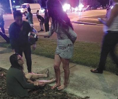从枪击案现场逃出后,伤者坐在路边,身上血迹可见。