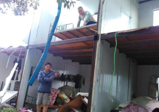 一个建筑工地的工人宿舍被大风摧毁,宿舍活动板房的墙壁被风刮飞。