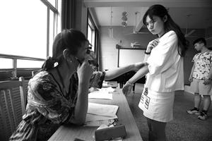 教师在看一名女孩手臂上的疤痕