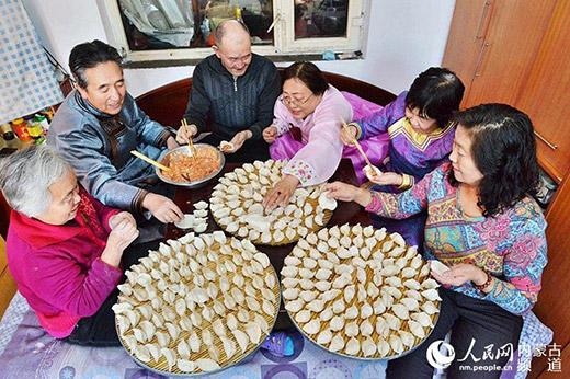 """图为呼和浩特市清泉街社区的少数民族住民围坐在一同包饺子:""""生计在这个社区的各族大众之间调和连合,各人设身处地以心换心,亲如一家心连心。""""(材料图)"""