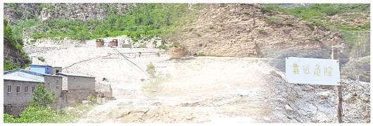 """金华隆矿公司在村当选厂厂房和尾矿库大坝,位于南款村内的一处尾矿库紧挨村道,简略的丝网围栏上挂着""""凑近风险""""的提醒牌。收集材料"""