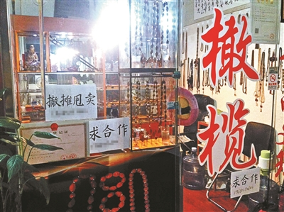 """大钟寺附近的爱家收藏市场,顾客稀少,有的店铺打出""""撤摊甩卖""""、""""求合作""""等告示"""