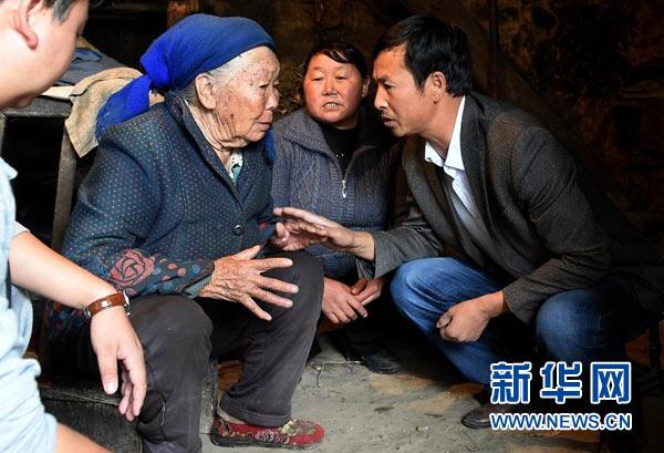 云南省曲靖市马龙县王家庄街道庄郎社区党支部书记张炳才(右一)在了解81岁的许留英老人的生活状况,为其制定精准脱贫方案(2016年6月3日摄)。新华社记者蔺以光 摄