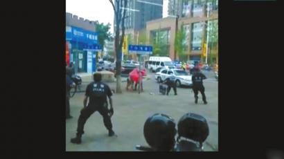 嫌疑人用床单和地毯将自己与人质包裹在一起,与特警对峙。(视频截图)