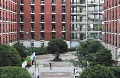 6月18日,昆明理工大学津桥学院,一位男生处置发的男生宿舍楼前走过。新京报记者 薛�B 摄