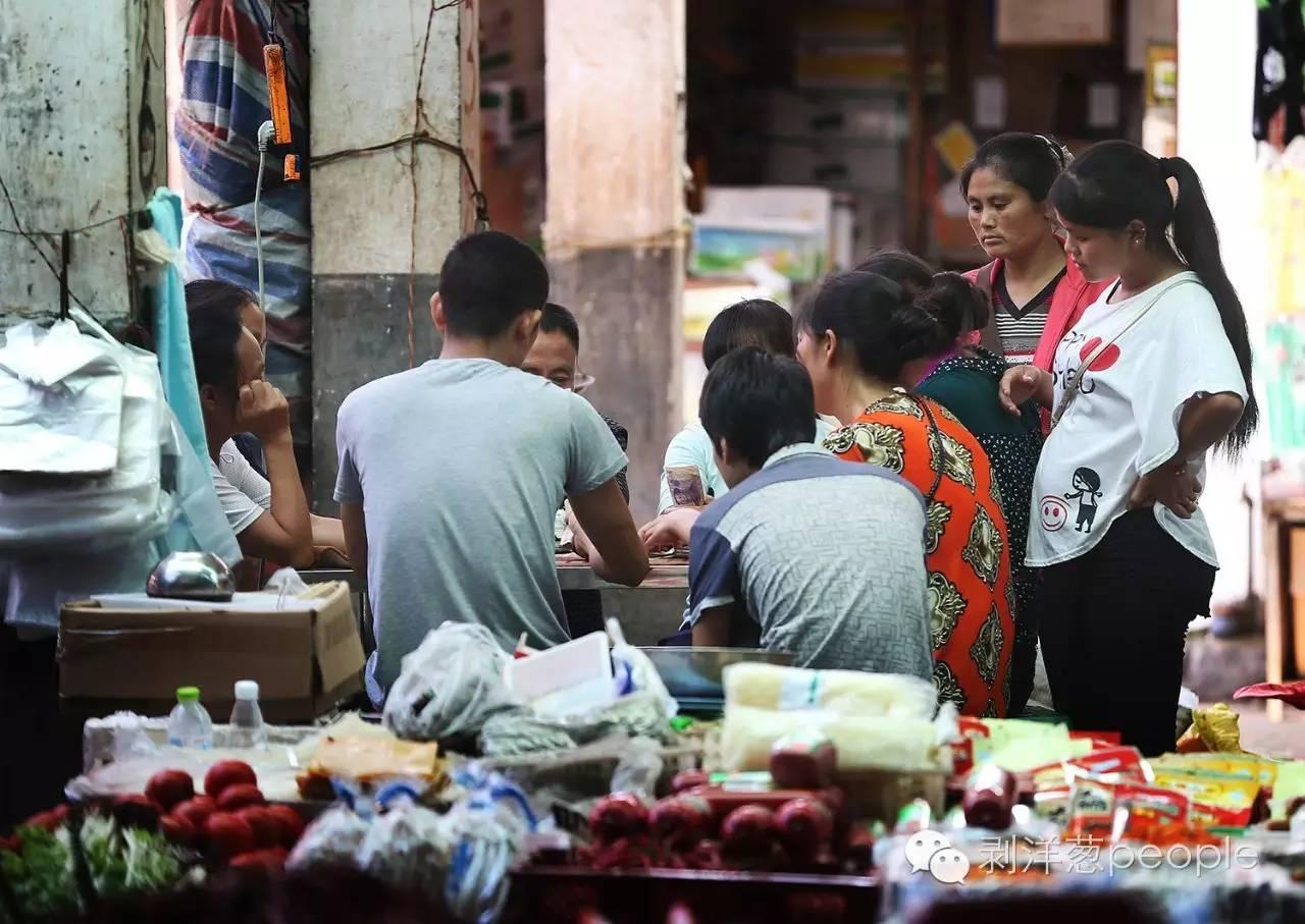 2016年6月20日,云南昭通盐津县庙坝镇的菜市场,人们围在菜摊间用扑克赌钱。新京报记者 尹亚飞 摄