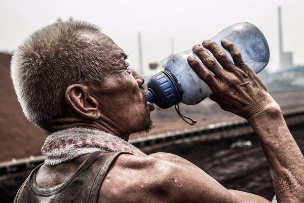 水壶里的水看着有点污浊,炎热的夏天工友们每天大量的体力劳动,身体的盐份会随着汗水快速的流失,为了保持体力大部分工友会在水壶中放些盐巴。