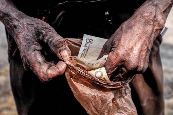 工友把钱仔细的放在塑料袋中保存着,以防汗水把工钱弄湿。