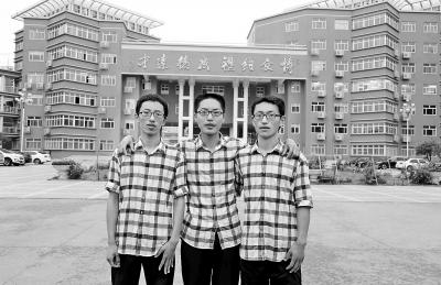 三胞胎在母校前合影。左是柯鑫垄,中是柯鑫堤,右是柯鑫圩。