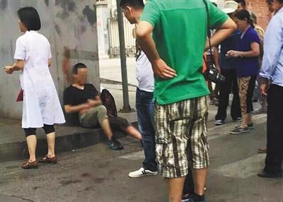 一位伤者依靠在桥墩旁,手捂腹部,腹部及左腿遍及鲜血。